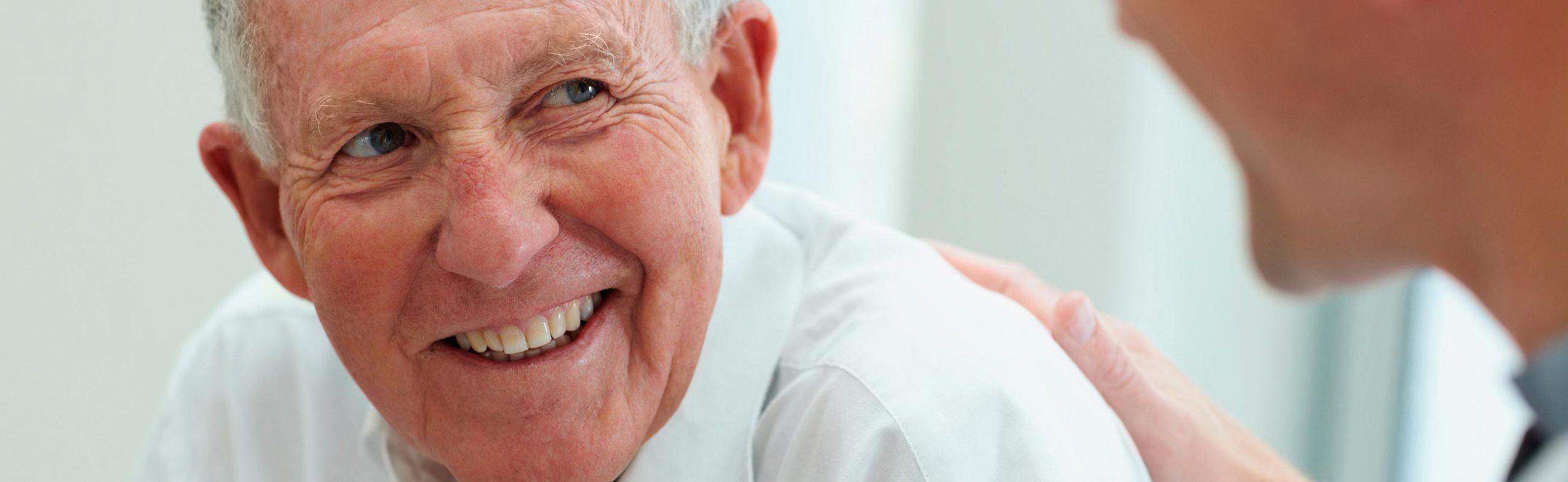 Älterer Mann lacht mit schönem Zahnersatz dank seines Zahnarztes in Bautzen.